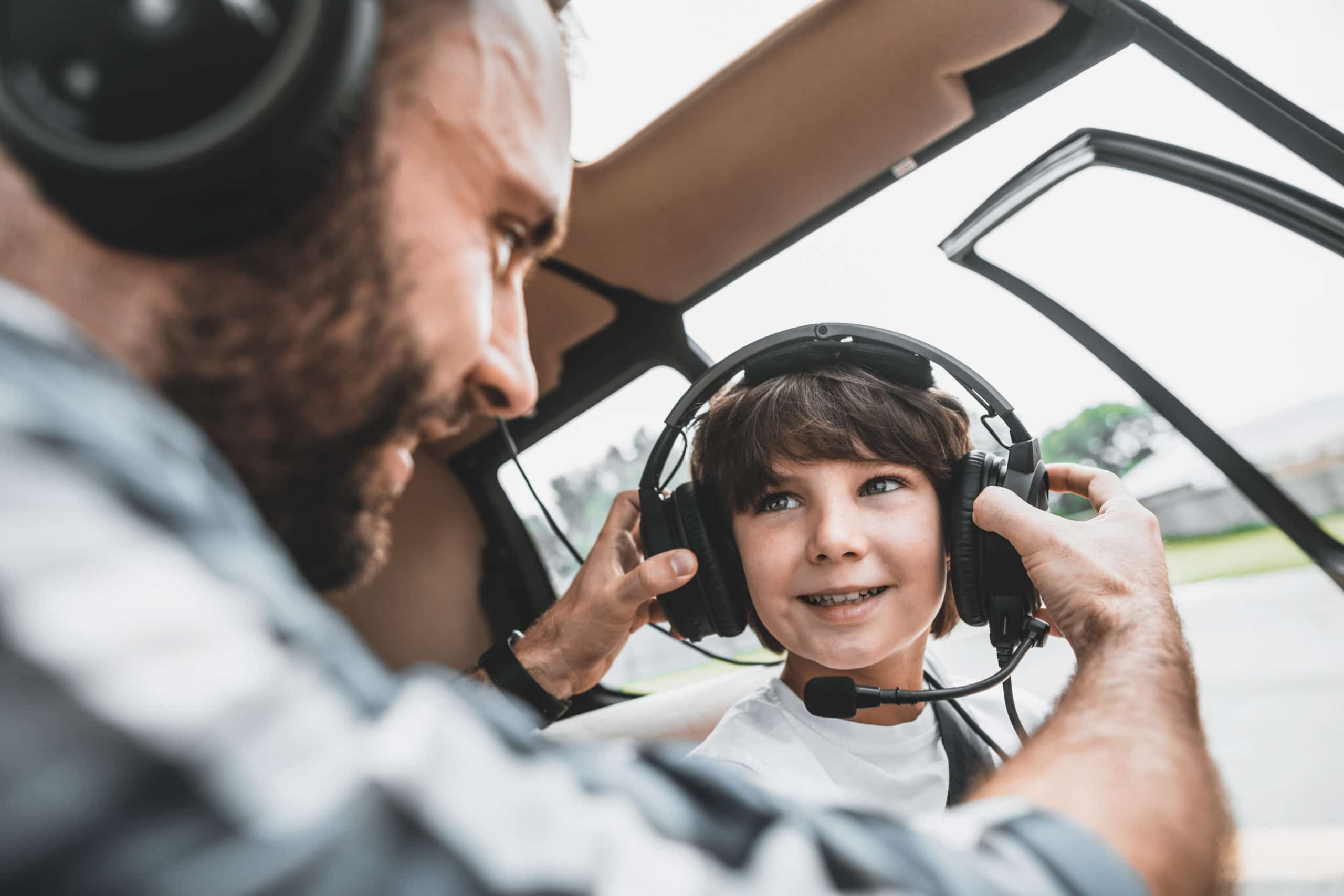 Satisfied bearded man putting modern headsets on cheerful boy while communicating with him. They sitting in modern helicopter inside